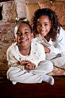 Two little African American sisters with happy smiles