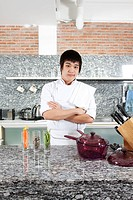 Asian young chef crossing arms in his kitchen.