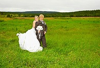 The bride and groom on nature in a green field
