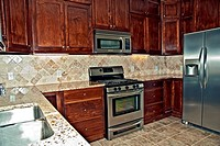 A new kitchen with tile and dark cabinets.