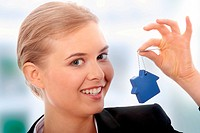 Young businesswoman holding house shaped key chain