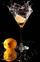 Splashing on martini with lemon isolated on blue background