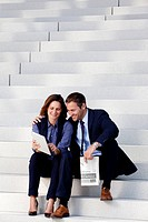 Businessman and businesswoman with tablet PC and newspaper on stairs