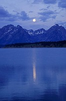 Grand Teton Mountains with full moon reflected in water