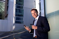 Smiling businessman with cell phone outdoors
