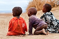Three children seen from behind, perching on folded knees, as they gaze into distance, one with naked buttocks exposed, Amboseli, Kenya, East Africa