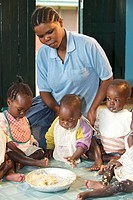 Infants eating with a children´s nurse in an orphanage near Bukoba, Tanzania, Africa