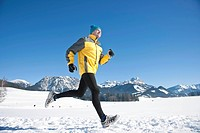 Woman jogging in the snow in the mountains