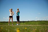 Two women joggers are standing by the side of the road and look at the view.