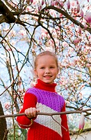 Happy small girl portrait near blossoming magnolia tree