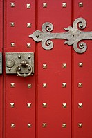 Red door of church with large brass hinge, door handle and other hardware