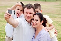 Happy family pilled together and taking self portrait on natural background