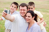 Cheerful family of five taking self portrait on natural background