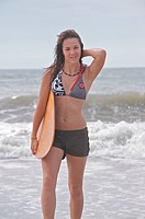 Athletic teen girl smiling and holding a skimboard while standing in the surf of the ocean.