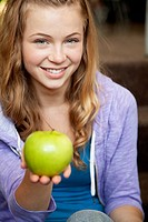 Girl holds out a green apple in the palm of her hand.