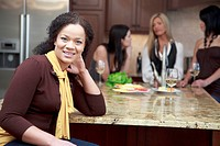 Attractive woman smiles in the kitchen as her friends converse in the background.