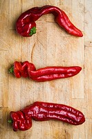 Three red chili peppers on a wooden chopping board