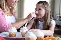 A woman and her young daughter are make cupcakes together.