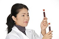 Beautiful Asian laboratory technician examining a tube of blood