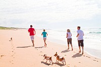 an active family running on beach with pets