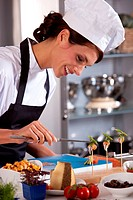 Attractive and happy female chef preparing an amuse