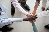 Group of businesspeople put their hands together for motivation.