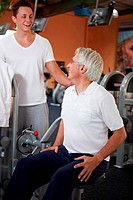 Eldery man doing back exercises in gym with fitness coach