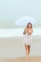 Beautiful woman near the stormy ocean at rain