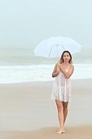 Beautiful woman near the stormy ocean at rain