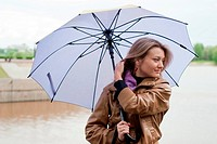 beauty girl in brown jacket and with violet umbrella on the river background