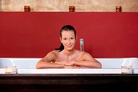 Young woman wellness bathing, smiling, looking at camera.