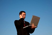 businessman talking at his cellular and working in the outdoor