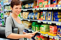 smiling woman choosing food at supermarket, all logos blurred