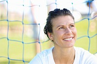Woman smiles while sitting in front of a soccer net.