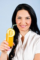 Young woman showing a smile face with white teeth and holding a glass with fresh orange juice