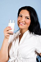 Beautiful happy young woman holding a full glass with milk and smiling you,concept of healthy lifestyle,on blue background