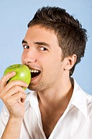 Young man taking bite og gree apple and looking you,on blue background