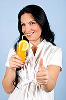 Healthy happy brunette woman giving thumbs up and holding a glass of fresh orange juice in hand,looking and smiling you dressed in white clothes on bl...