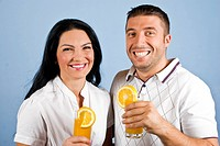 Extremely happy healthy couple laughing and holding glasses with fresh oranges juice on blue background