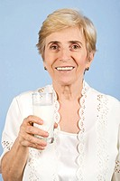 Healthy old woman holding a glass milk and smiling for you on blue background