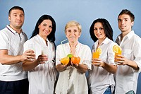 Healthy group of friends people or family persons standing in a line and holding different fruits, fresh orange juice or milk in glasses,all people we...