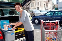 customer woman loading car with food at supermarket car park