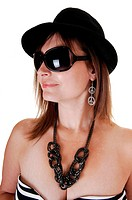 A closeup portrait of a middle aged woman with a black hat and big sunglasses a nice necklace and earrings, in profile.