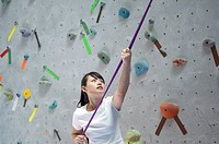 Woman looks up while bracing a rope on a climbing wall.