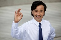 Asian businessman giving the ok sign to the camera.
