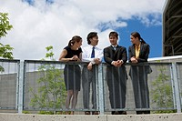 Businesspeople leaning on a railing together.