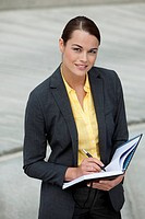 Businesswoman standing outside with a planner and smiling.