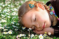 Young girl sleeping in a meadow of daisy flowers