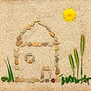 House illustration in sand made of pebbles, grass and flowers