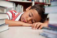Schoolboy sleeps with his head down at a library table.